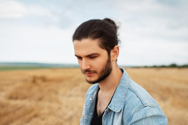 Ritratto di giovane uomo che guarda in basso nel campo di grano.