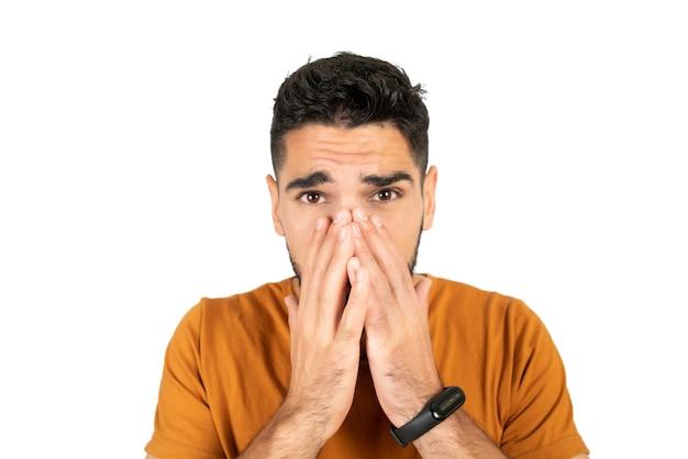 Ritratto di giovane uomo che guarda spaventato e che copre il viso su sfondo bianco in studio.