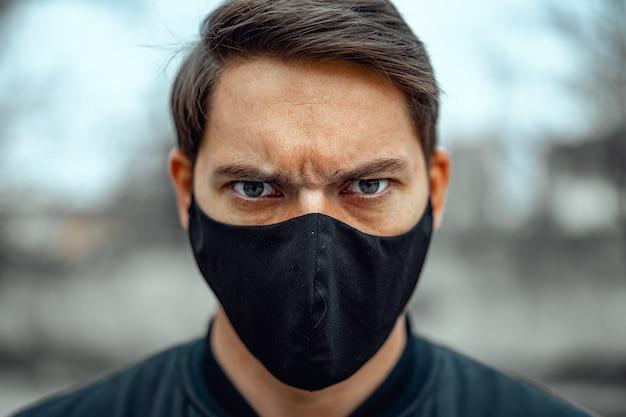 Ritratto di giovane uomo in maschera medica per le strade. prevenzione del coronavirus