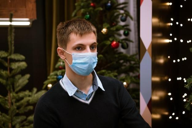 Ritratto di un giovane uomo in una maschera medica e un maglione contro bokeh e un albero di natale