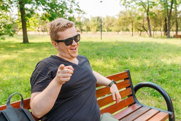 Ritratto di un giovane uomo nel parco. espressione facciale di emozione. sorriso, sentimenti e reazione delle persone. sorriso psicopatico omicida.