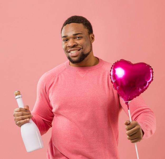 Ritratto di giovane uomo alla festa con palloncino e bottiglia di champagne