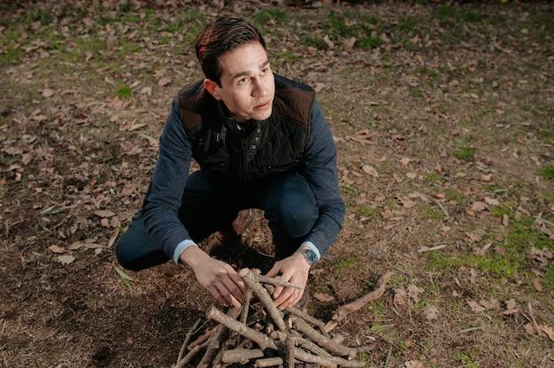 Ritratto di giovane uomo che prepara catasta di legna per accendere il fuoco. campeggio, concetto di stile di vita naturale.