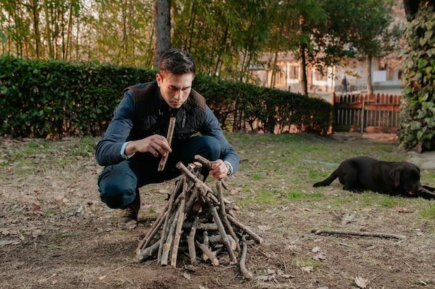 Ritratto di giovane uomo che prepara catasta di legna per accendere il fuoco. cane da campeggio, concetto di stile di vita naturale.