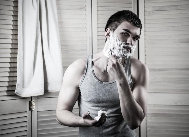Ritratto di un giovane uomo che si rade la faccia in bagno durante l'igiene mattutina