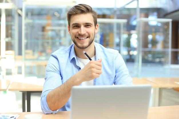 Ritratto di giovane uomo seduto alla sua scrivania in ufficio.