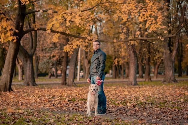 Ritratto di giovane uomo seduto che abbraccia con il cane golden retriever. amicizia, animale domestico e umano. uomo che gioca con il cane