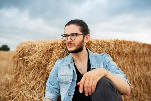 Ritratto di giovane uomo seduto vicino a mucchi di fieno sullo sfondo delle nuvole.