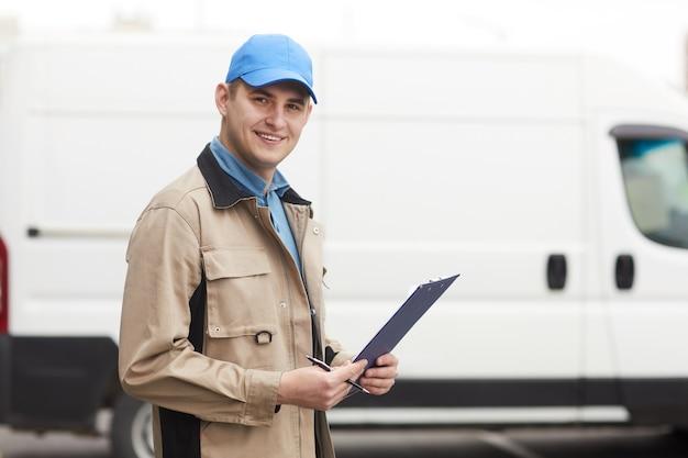 Ritratto di giovane uomo che sorride alla macchina fotografica mentre levandosi in piedi all'aperto che lavora nella società di consegna