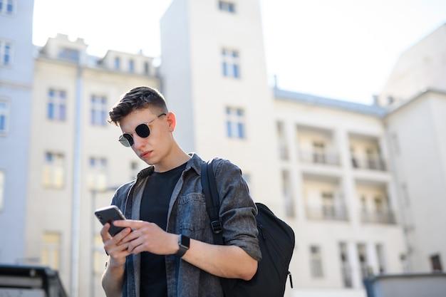 Un ritratto di giovane uomo in piedi all'aperto in città, utilizzando lo smartphone.