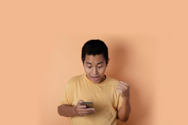 Il ritratto del giovane che sta usando il telefono cellulare fa il gesto del vincitore su fondo arancione.