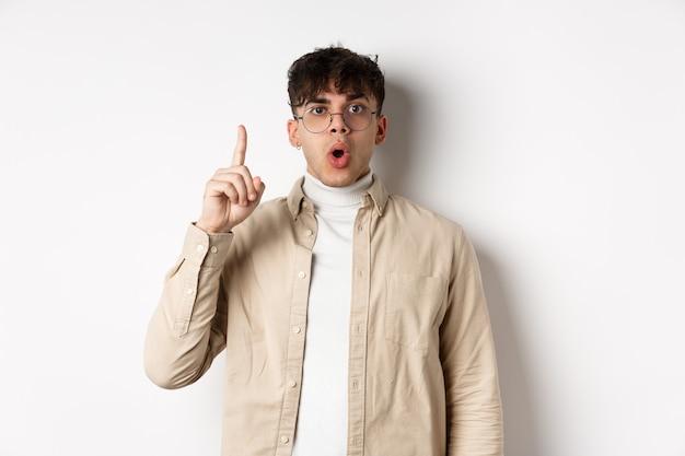 Ritratto di giovane studente che lancia un'idea, alza il dito e dice suggerimento, ha un piano, in piedi sul muro bianco in occhiali e abiti casual.
