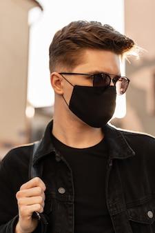 Ritratto di giovane uomo con occhiali da sole in abiti eleganti con maschera protettiva nera in una luminosa giornata di primavera