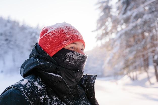 Ritratto di un giovane uomo in una soleggiata giornata invernale sullo sfondo di una foresta innevata