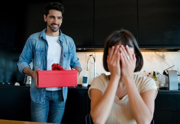 Ritratto di giovane uomo che sorprende la sua ragazza con una confezione regalo.