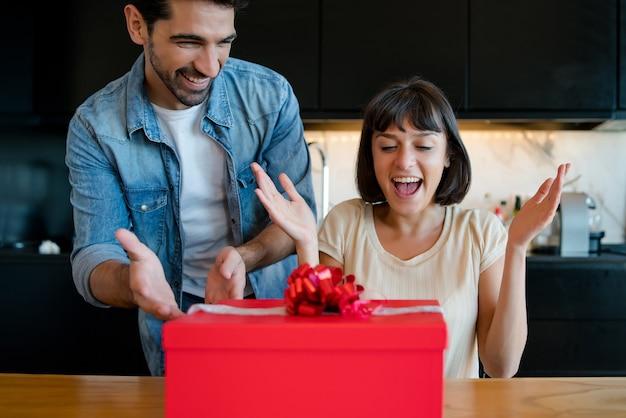Ritratto di giovane uomo sorprendente la sua ragazza con una confezione regalo.
