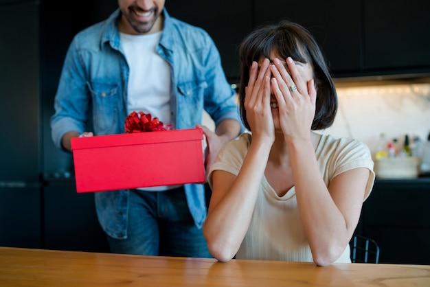 Ritratto di giovane uomo sorprendente la sua ragazza con una confezione regalo