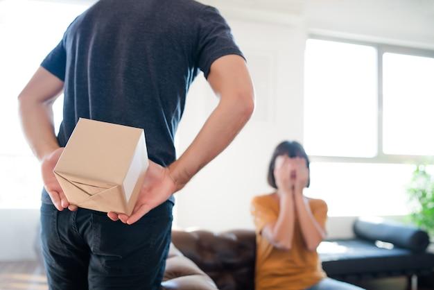 Ritratto di giovane uomo che sorprende la sua ragazza con un regalo