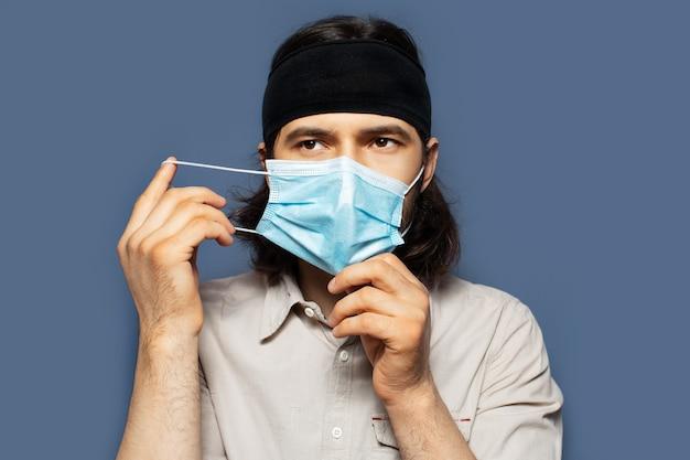 Ritratto di giovane che si toglie la maschera medica dal viso su sfondo di colore blu. vista del primo piano della foto dello studio.