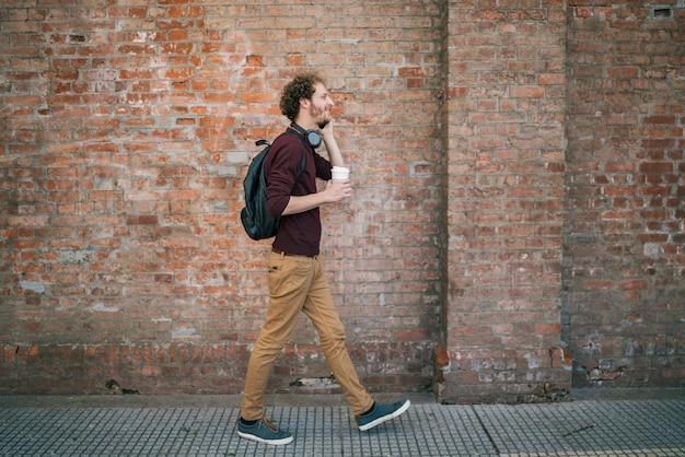 Ritratto di giovane uomo che parla al telefono mentre si cammina all'aperto in strada. comunicazione e concetto urbano.