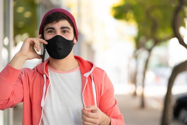 Ritratto di giovane uomo che parla al telefono mentre si cammina all'aperto sulla strada. uomo che indossa la maschera per il viso. concetto urbano.