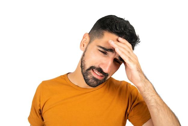 Ritratto di giovane uomo stanco e soffre di mal di testa in studio. sfondo bianco isolato.