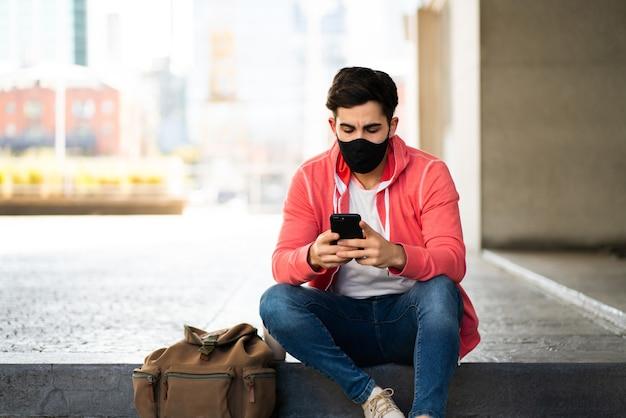 Ritratto di giovane uomo utilizzando il suo telefono cellulare mentre è seduto all'aperto in strada. uomo che indossa la maschera per il viso. concetto urbano.