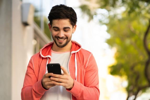 Ritratto di giovane uomo utilizzando il suo telefono cellulare mentre si cammina all'aperto sulla strada. concetto urbano.
