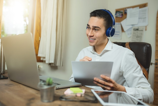 Ritratto di giovane uomo in videochiamata con laptop e cuffie, in possesso di un documento e mostrando qualcosa.