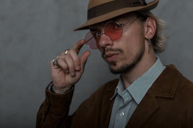 Ritratto di un giovane uomo con un cappello vintage in una giacca elegante in una camicia con la barba. ragazzo regola gli occhiali e guarda la telecamera. abbigliamento da uomo.
