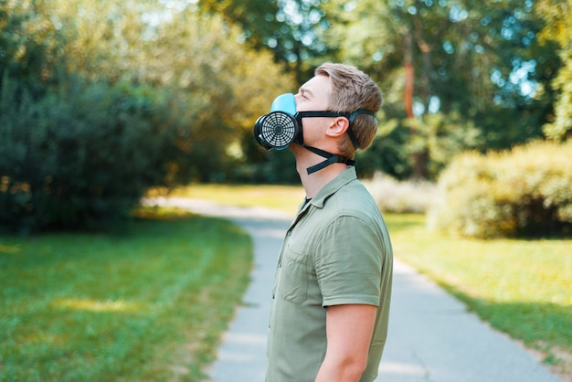 Ritratto di giovane uomo che cammina nel parco e indossa un respiratore, sii sicuro covid19.