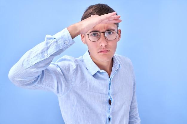 Ritratto di un giovane uomo con gli occhiali vestito in camicia di affari che guarda lontano con entusiasmo con la mano sopra la testa. ricerca concetto isolato su sfondo blu in studio