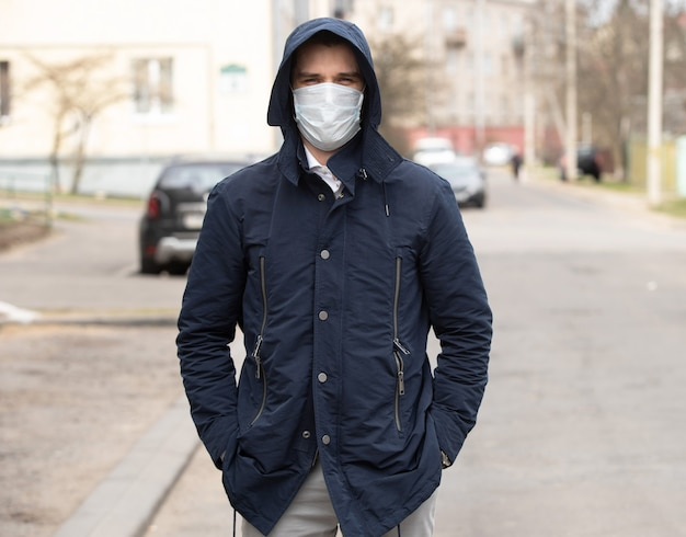 Ritratto di un giovane uomo che indossa la maschera protettiva sulla strada