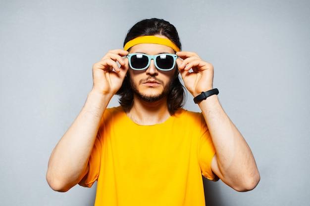Ritratto di giovane uomo che indossa occhiali da sole, fascia gialla per la testa e camicia sullo sfondo di una parete grigia strutturata.
