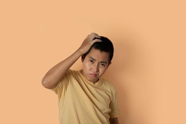 Ritratto di giovane uomo che indossa t-shirt sentirsi deluso su sfondo arancione con copia spazio.
