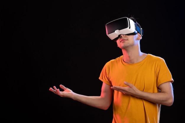 Ritratto di giovane uomo che indossa la parete scura delle cuffie per realtà virtuale