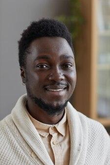Ritratto di giovane uomo in maglione bianco sorridente davanti