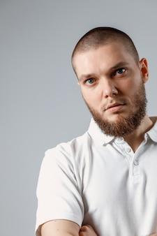 Ritratto del giovane in una maglietta bianca seriamente su gray