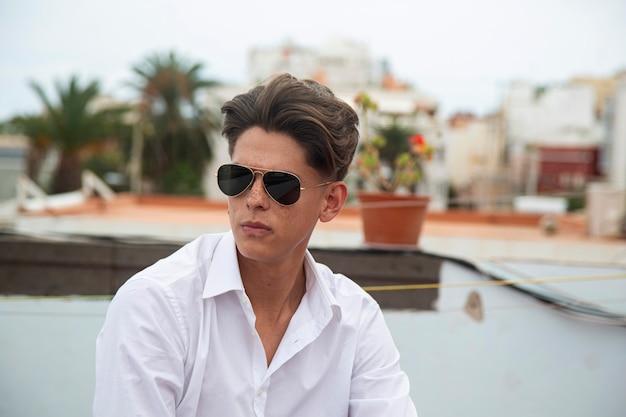 Ritratto di giovane uomo con gli occhiali da aviatore sul tetto.