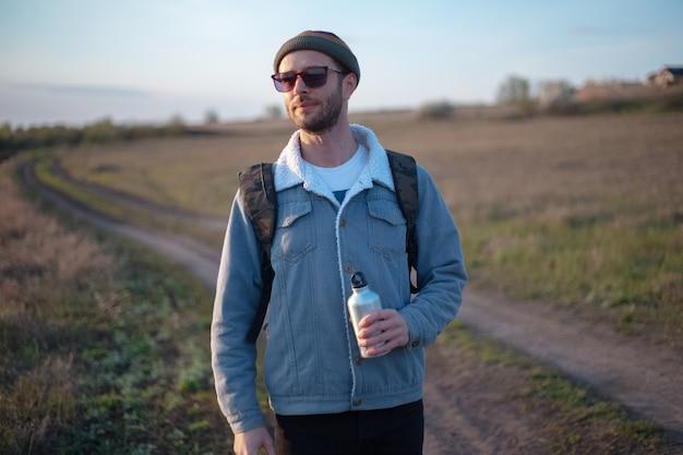 Ritratto di giovane uomo con zaino tenendo in mano una bottiglia d'acqua termica in alluminio riutilizzabile