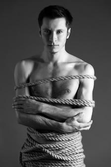 Ritratto di giovane uomo con corpo legato con le corde
