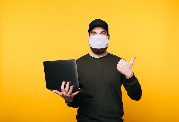 Ritratto del giovane con la maschera facciale facendo uso del computer portatile e mostrando i pollici su via