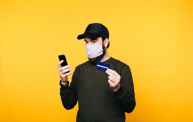 Ritratto di giovane uomo con maschera facciale e l'utilizzo di smartphone con carta di credito