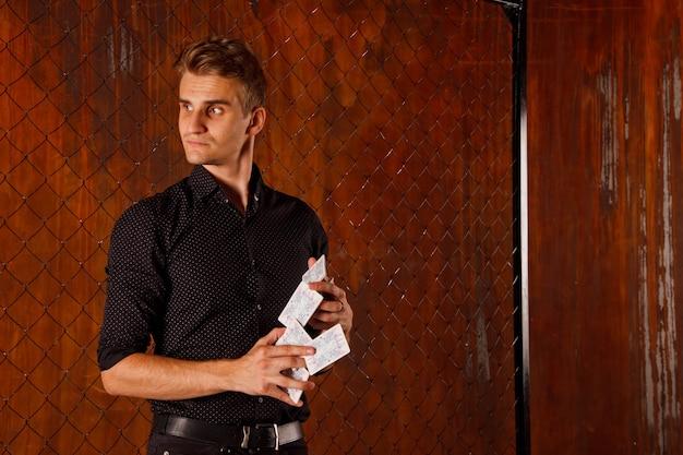 Ritratto di giovane uomo con carte da gioco al cancello. bel ragazzo mostra trucchi con la carta. mani intelligenti di mago