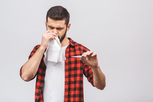 Ritratto di un giovane con fazzoletto e termometro. ragazzo malato isolato ha il naso che cola. l'uomo fa una cura per il raffreddore e l'influenza.
