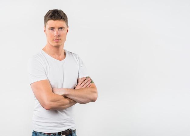 Il ritratto di un giovane con il suo braccio ha attraversato lo sguardo alla macchina fotografica contro fondo bianco