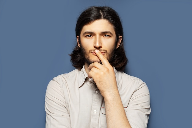 Ritratto di giovane uomo con i capelli lunghi su sfondo blu.