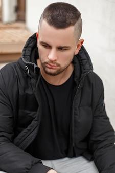 Ritratto di un giovane uomo con i capelli corti in una calda giacca invernale si siede sulle scale