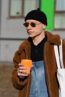 Ritratto di giovane uomo con occhiali da sole e berretto e tazza di caffè arancione