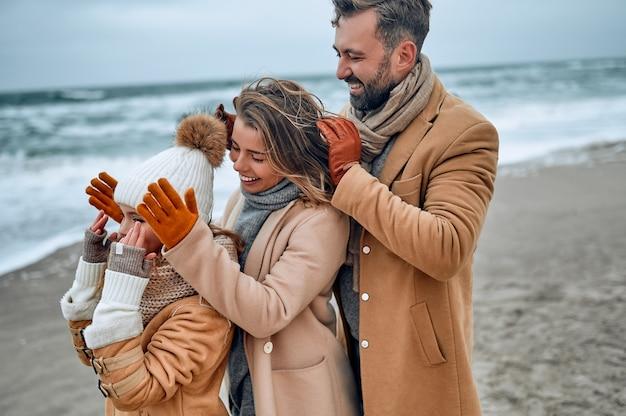 Ritratto di una giovane coppia sposata e della loro figlia carina che si divertono sulla spiaggia in inverno indossando vestiti caldi e sciarpe nella stagione fredda.
